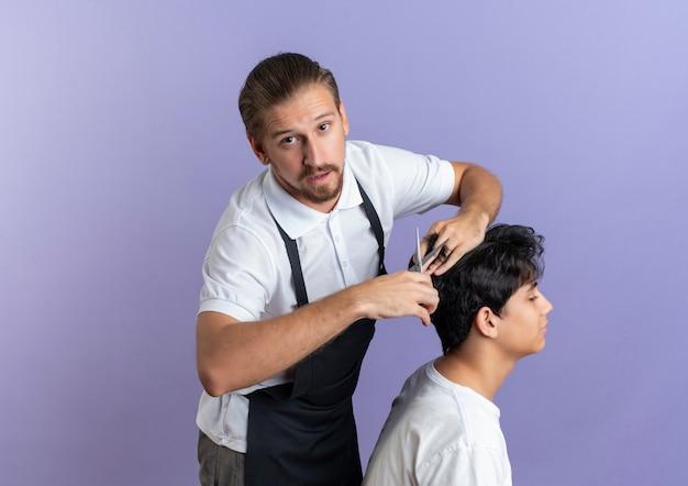 コピースペースで紫に分離された若いクライアントのために散髪をしている制服を着ている感動の若いハンサムな床屋