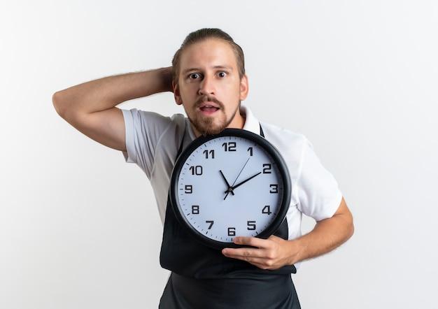 Impressionato giovane barbiere bello che indossa l'orologio uniforme della tenuta che mette la mano dietro la testa isolata su bianco Foto Gratuite