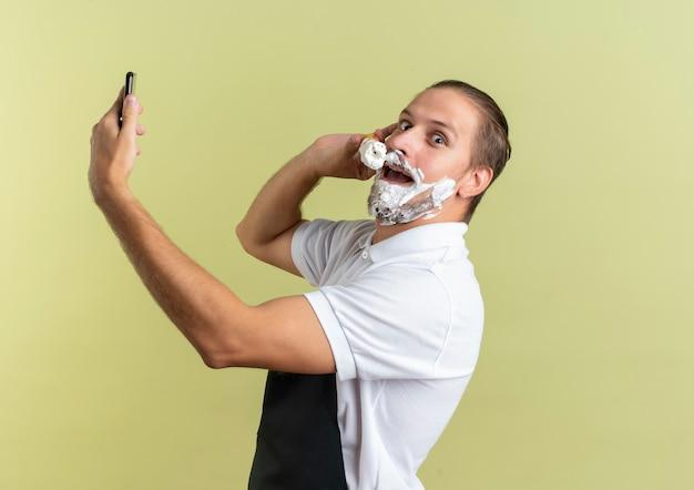 감동적인 젊은 잘 생긴 이발사 유니폼을 입고 휴대 전화를 들고 복사 공간이 올리브 녹색에 고립 된 자신의 수염에 면도 크림을 적용