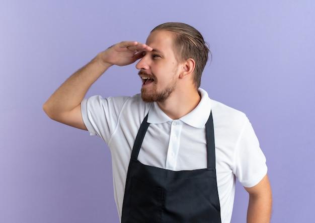 紫色で隔離された距離を見て目の上に手を保ちながら制服を着ている感動の若いハンサムな理髪師