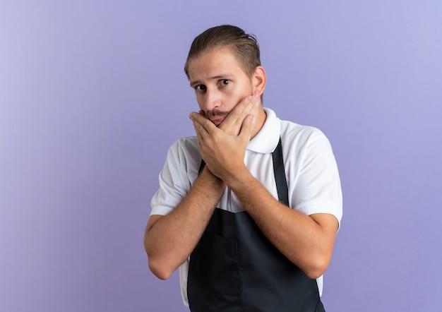 コピースペースで紫に分離されたあごに手を置く制服を着ている感動の若いハンサムな理髪師