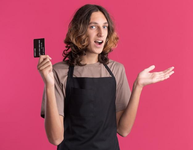 カメラにクレジットカードを示し、空の手を示す制服を着た若いハンサムな理髪師に感銘を受けました