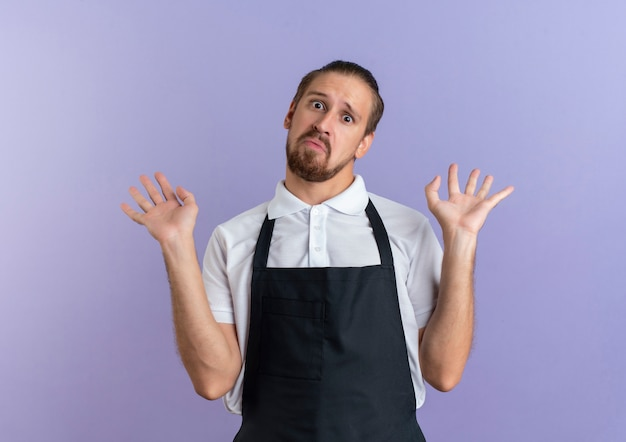 紫色で隔離された空の手を示す制服を着て感動した若いハンサムな理髪師