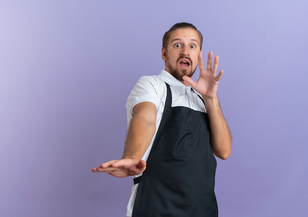 Impressed young handsome barber wearing uniform stretching out hand gesturing no isolated on purple  with copy space