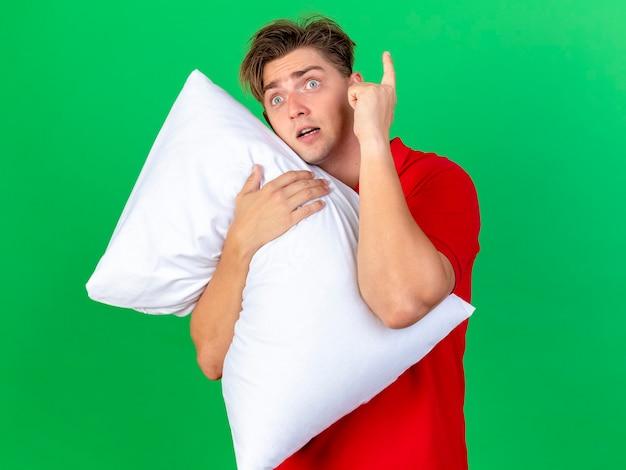 コピースペースで緑の壁に分離されたまっすぐに指を上げる枕を保持している印象的な若いハンサムな金髪の病気の男