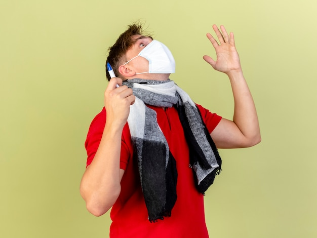 올리브 녹색 벽에 고립 된 공기에 손을 유지 찾고 온도계를 들고 마스크와 스카프를 착용하는 감동 젊은 잘 생긴 금발 아픈 남자