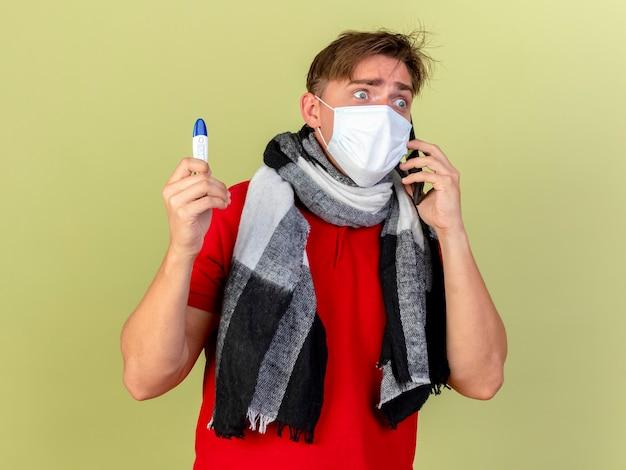올리브 녹색 벽에 고립 된 측면을보고 전화로 얘기하는 온도계를 들고 마스크와 스카프를 착용하는 감동 된 젊은 잘 생긴 금발 아픈 남자