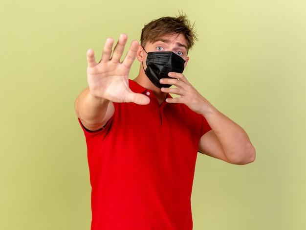 印象的な若いハンサムな金髪の病気の男は、マスクを着用し、コピースペースのあるオリーブグリーンの壁に孤立して手を伸ばしています