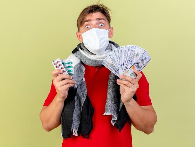 Impressionato giovane uomo malato biondo bello che indossa la maschera che tiene soldi e confezioni di pillole mediche isolate sulla parete verde oliva