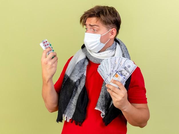 Impressionato giovane uomo malato biondo bello che indossa maschera e sciarpa tenendo i soldi e le pillole guardando le pillole isolate su sfondo verde oliva