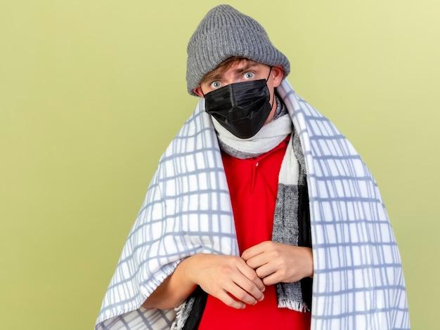 コピースペースでオリーブグリーンの背景に分離されたカメラを見て格子縞に包まれたマスクの冬の帽子とスカーフを身に着けている印象的な若いハンサムな金髪の病気の男
