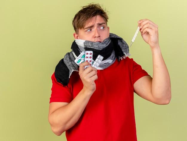 복사 공간 올리브 녹색 벽에 고립 된 온도계를 찾고 의료 약과 온도계를 들고 스카프를 착용하는 감동 젊은 잘 생긴 금발 아픈 남자