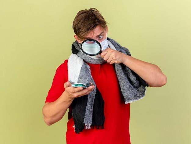 オリーブグリーンの背景に分離された拡大鏡でそれらを見て医療薬を保持しているスカーフを身に着けている印象的な若いハンサムな金髪の病気の男