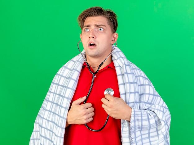 緑の壁に隔離された側を見て彼自身の心拍を聞いて聴診器を身に着けている感動の若いハンサムな金髪の病気の男