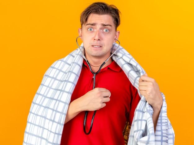オレンジ色の壁に分離された彼自身の心拍を聞いて格子縞に包まれた聴診器を身に着けている感動した若いハンサムな金髪の病気の男