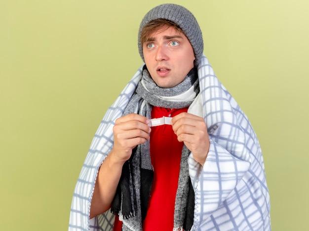 コピースペースでオリーブグリーンの背景に分離された側を見て格子縞の保持石膏に包まれた冬の帽子とスカーフを身に着けている印象的な若いハンサムな金髪の病気の男