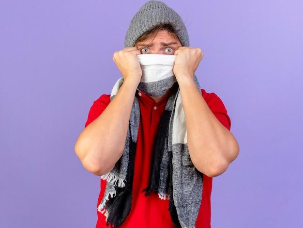 Impressionato giovane uomo malato biondo bello che indossa cappello invernale e sciarpa che copre la bocca con sciarpa isolata sulla parete viola con lo spazio della copia