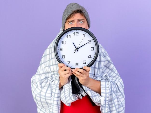 Impressionato giovane bello biondo malato che indossa un cappello invernale e sciarpa avvolto in un plaid tenendo l'orologio guardando la telecamera da dietro isolato su sfondo viola