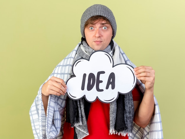 Impressed young handsome blonde ill man wearing winter hat and scarf wrapped in plaid holding idea bubble looking at camera isolated on olive green background