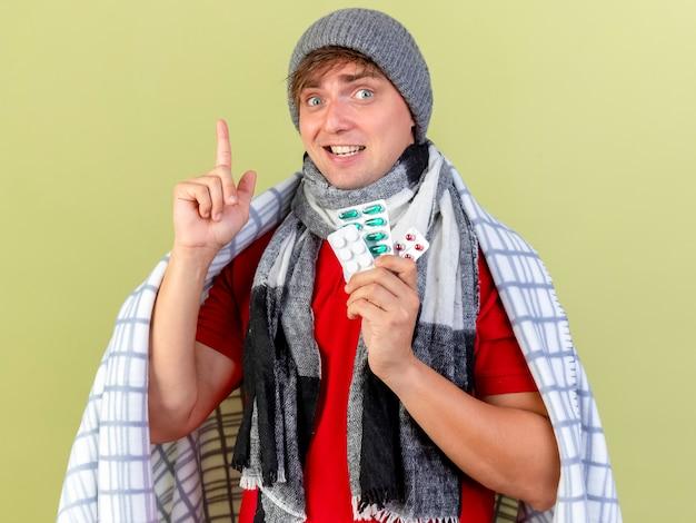 Impressionato giovane bello biondo malato che indossa cappello invernale e sciarpa avvolto in plaid che tiene confezioni di pillole mediche rivolte verso l'alto isolato sulla parete verde oliva