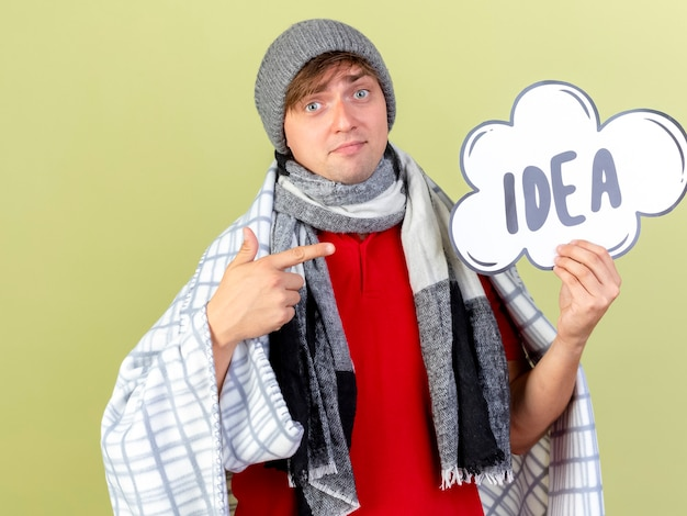 Impressed young handsome blonde ill man wearing winter hat and scarf wrapped in plaid holding and pointing at idea bubble  isolated on olive green wall