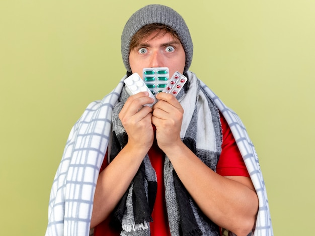 Impressionato giovane bello biondo malato che indossa cappello invernale e sciarpa avvolta in plaid toccando la bocca con confezioni di pillole mediche che guarda l'obbiettivo isolato su sfondo verde oliva