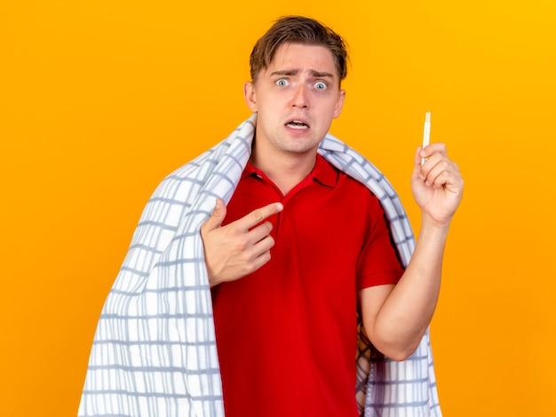 オレンジ色の壁に隔離された温度計を保持し、指している格子縞に包まれた感動の若いハンサムな金髪の病気の男