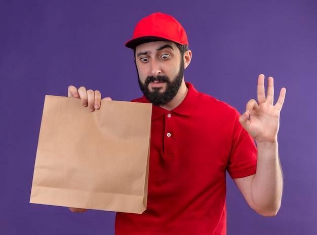 赤い制服と帽子を身に着けて紙のパッケージを保持し、見て、紫で隔離のokサインをしている印象的な若いハンサムな白人配達人