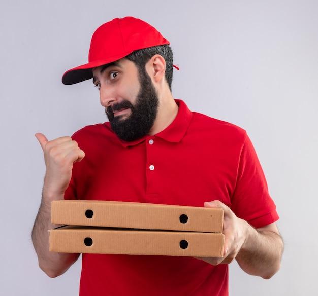 빨간 유니폼과 모자를 입고 피자 상자를 들고 뒤에 고립 된 흰색을 가리키는 감동 젊은 잘 생긴 백인 배달 남자