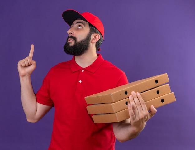 빨간 유니폼과 모자를 찾고 피자 상자를 들고 보라색에 고립 가리키는 감동 젊은 잘 생긴 백인 배달 남자