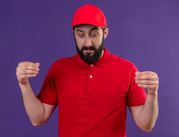 Впечатленный молодой красивый кавказский доставщик в красной форме и кепке притворяется, что держит что-то, глядя вниз, изолированное от фиолетового