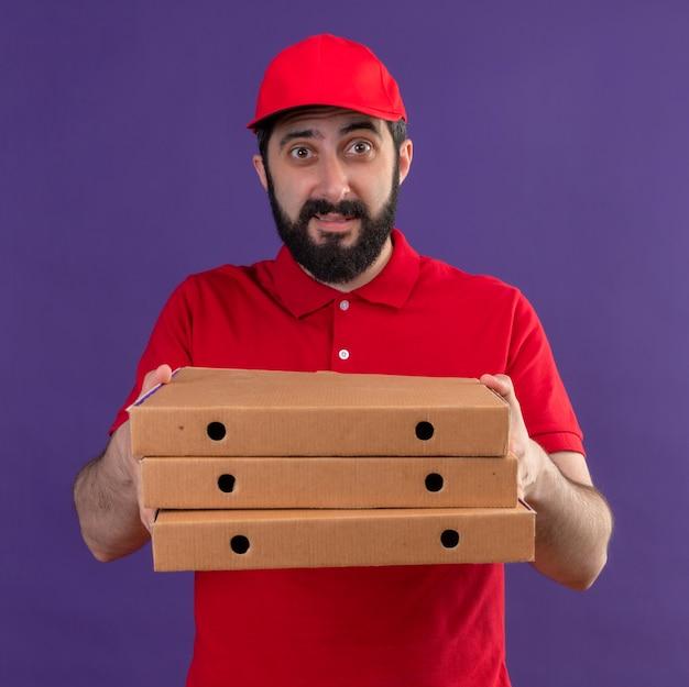 赤い制服と紫で隔離のピザの箱を伸ばしてキャップを身に着けている感動若いハンサムな白人配達人