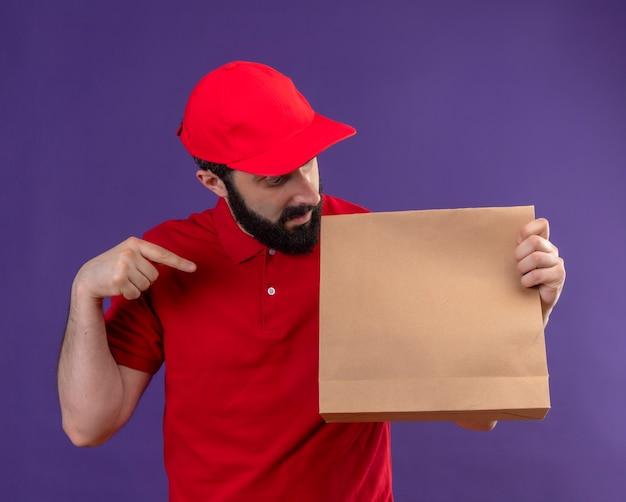 Impressionato giovane uomo di consegna caucasico bello che indossa uniforme rossa e berretto che tiene guardando e indicando il pacchetto di carta isolato sulla porpora