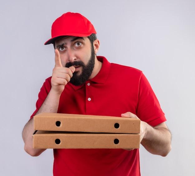 Impressionato giovane uomo di consegna caucasico bello che indossa l'uniforme rossa e il cappuccio che tiene le scatole per pizza che indicano e che cercano isolato su bianco