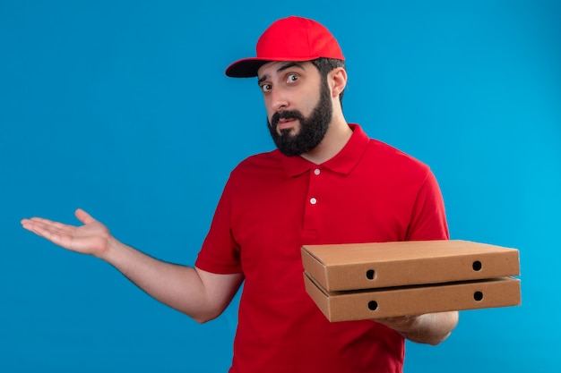 Impressed young handsome caucasian delivery man wearing red uniform and cap holding pizza boxes and showing empty hand isolated on blue