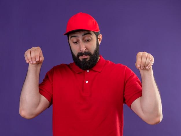 Il giovane uomo caucasico bello di consegna impressionato che porta l'uniforme rossa e il berretto finge di tenere qualcosa che guarda giù isolato sulla porpora