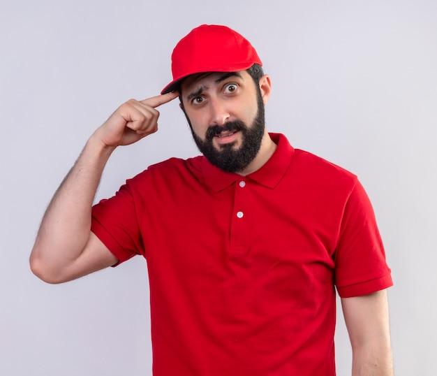 Impressionato giovane uomo di consegna caucasico bello che indossa l'uniforme rossa e cappuccio che mette il dito sul tempio isolato su bianco