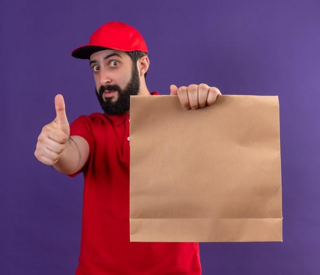Colpito il giovane uomo di consegna caucasico bello che indossa l'uniforme rossa e il cappuccio che allunga il pacchetto di carta verso la macchina fotografica isolata sulla porpora