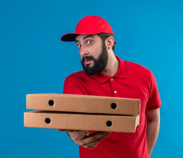 Impressionato giovane uomo di consegna caucasico bello che indossa l'uniforme rossa e cappuccio che allunga le scatole per pizza verso la telecamera isolata sull'azzurro
