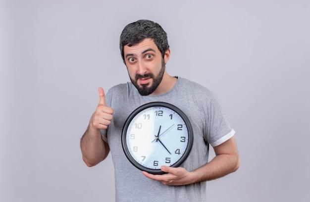 Impressionato giovane uomo caucasico bello che tiene l'orologio e che mostra il pollice su isolato su bianco con lo spazio della copia