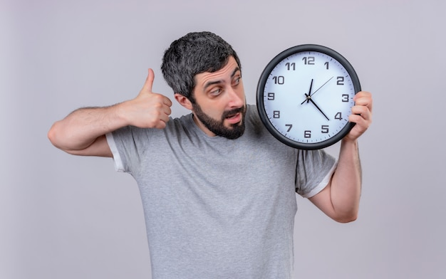 Impressionato giovane uomo caucasico bello che tiene e che guarda l'orologio e che mostra il pollice su isolato su bianco