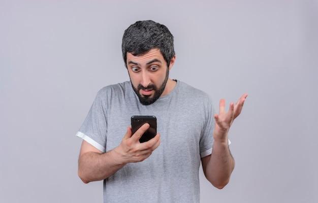 Impressionato giovane uomo caucasico bello che tiene e che esamina il telefono cellulare con la mano alzata isolata su bianco con lo spazio della copia