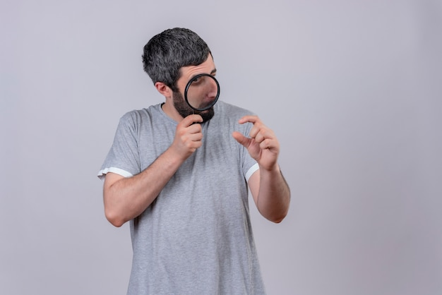 Impressed young handsome caucasian man holding and looking through magnifying glass with one eye closed and showing size isolated on white  with copy space