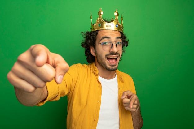 Impressionato giovane uomo caucasico bello con gli occhiali e corona che guarda l'obbiettivo che ti fa gesto isolato su priorità bassa verde con lo spazio della copia