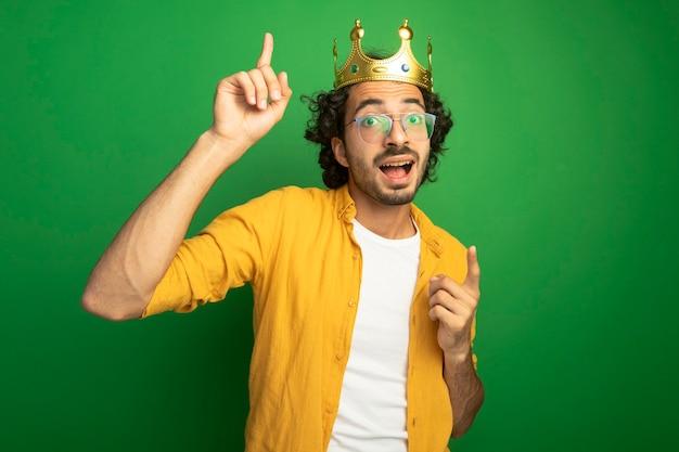 Impressionato giovane uomo caucasico bello con gli occhiali e corona che guarda l'obbiettivo rivolto verso l'alto isolato su sfondo verde con spazio di copia