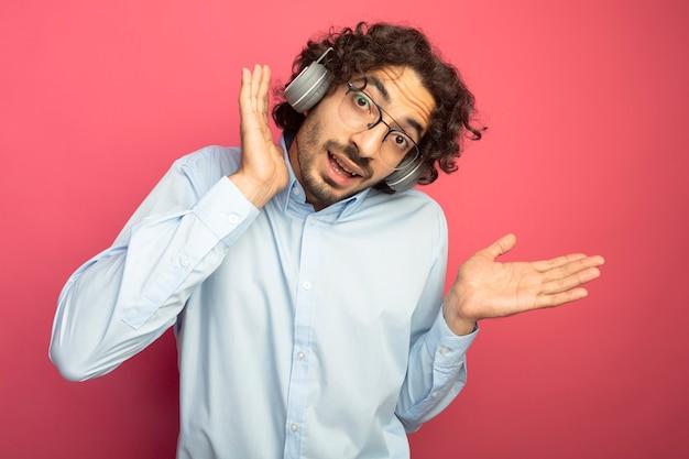 Impressionato giovane uomo caucasico bello con gli occhiali e le cuffie che guarda l'obbiettivo tenendo la mano vicino alla testa che mostra la mano vuota isolata su sfondo cremisi