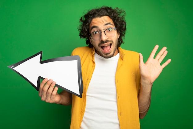 緑の壁に隔離された空の手を示す側を指している矢印マークを保持している眼鏡をかけている印象的な若いハンサムな白人男性