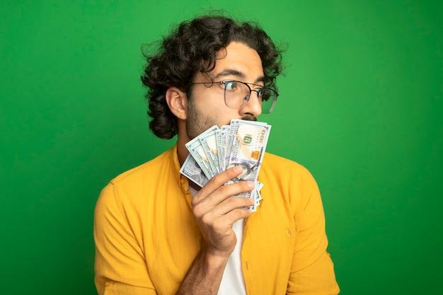 Impressionato giovane uomo caucasico bello con gli occhiali che tengono i soldi davanti alla bocca guardando il lato isolato sulla parete verde con lo spazio della copia