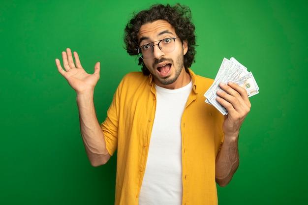 Impressionato giovane uomo caucasico bello con gli occhiali che tengono i soldi che mostrano la mano vuota che guarda l'obbiettivo isolato su priorità bassa verde