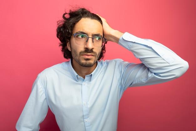 真っ赤な背景で隔離された側を見て頭に手を置いて眼鏡をかけている印象的な若いハンサムな白人男性